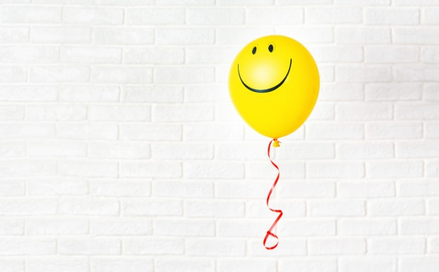 Yellow ballon with smile hangs aganst white wall