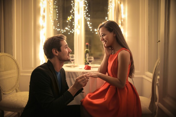 Handsome man proposing a beautiful woman to marry him