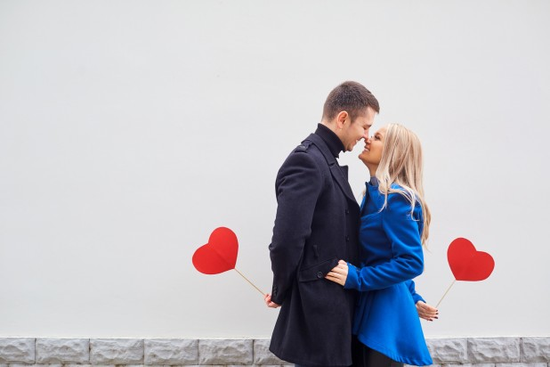A loving couple in a coat with hearts in hands.